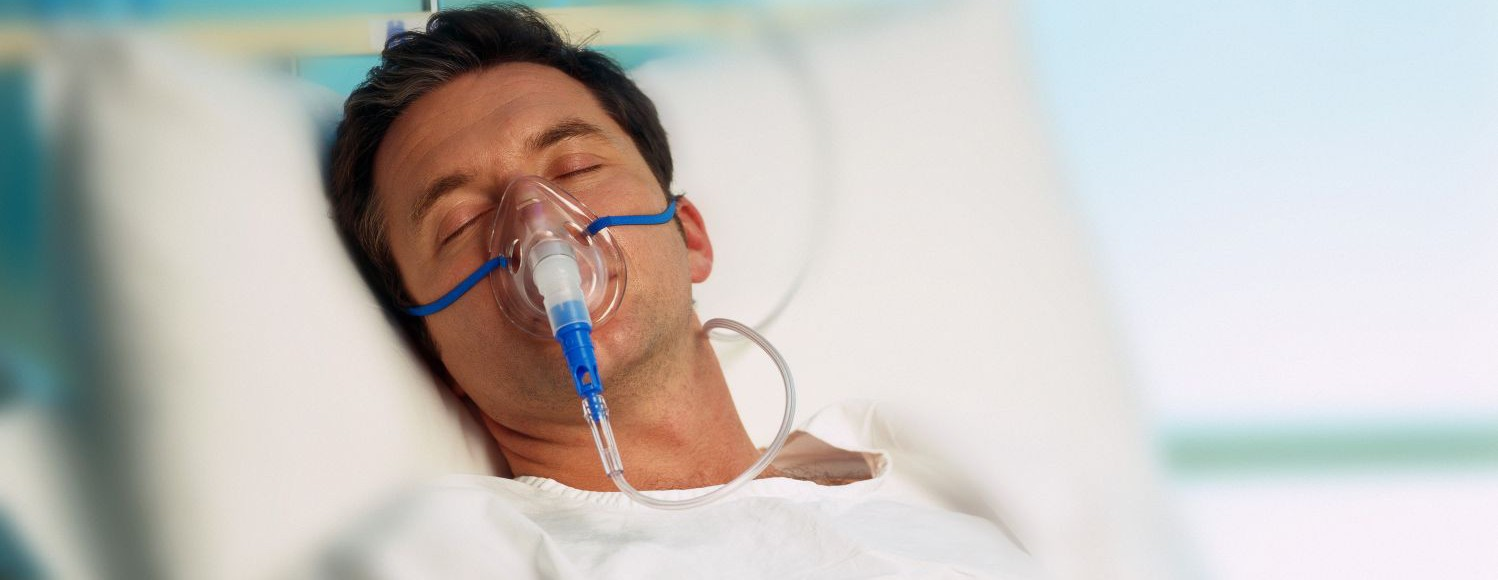 Portrait of a man with an oxygen mask in a hospital bed
